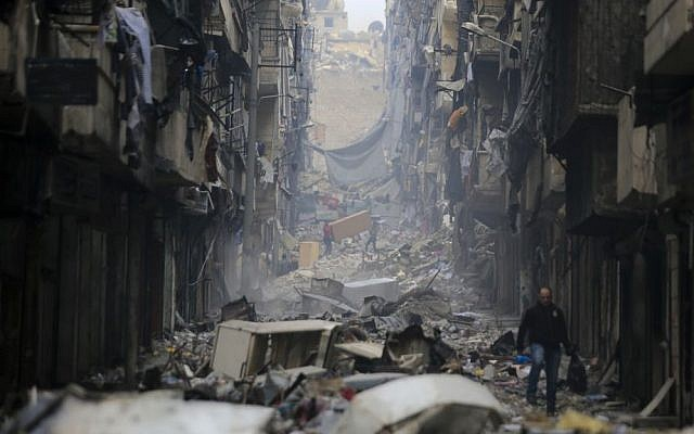 In this January 20, 2017 photo, residents walk amid the rubble of the once rebel-held Salaheddine neighborhood of eastern Aleppo, Syria. (AP Photo/Hassan Ammar)