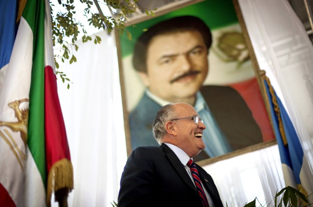 Former New York City Mayor Rudy Giuliani walks under a photo of Iran opposition leader Massoud Rajavi as he takes the podium to speak at a protest of Iranian President Mahmoud Ahmadinejad's visit to the United Nations, in New York, Thursday, Sept. 23, 2010. (AP Photo/David Goldman)