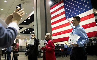 In this Wednesday, Feb. 15, 2017, file photo, Erik Danialian, a 21-year-old immigrant from Iran, poses with his US citizenship certificate in front of a large US flag after a naturalization ceremony at the Los Angeles Convention Center, in Los Angeles, California. (AP Photo/Jae C. Hong, File)
