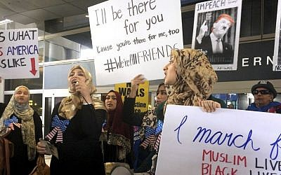 Protesters against US President Donald Trump's temporary travel ban on citizens from seven Muslim-majority nations stand in front of the Bradley Terminal at Los Angeles International Airport, Saturday, Feb. 4, 2017, in Los Angeles. (AP Photo/Reed Saxon)