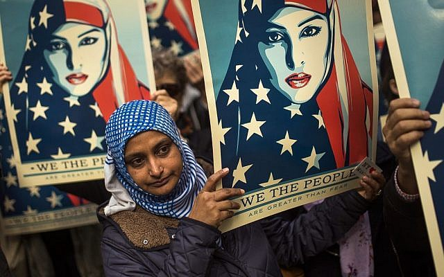 People carry posters during a rally against President Donald Trump's executive order banning travel from seven Muslim-majority nations, in New York's Times Square, Sunday, Feb. 19, 2017. (AP Photo/Andres Kudacki)