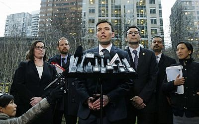 Washington state Solicitor General Noah Purcell, center, talks to reporters as Attorney General Bob Ferguson, third from right, looks on, Friday, Feb. 3, 2017, following a hearing in federal court in Seattle.(AP Photo/Ted S. Warren)