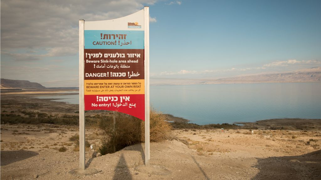 A sign warning visitors of the danger of sinkholes around the shores of the Dead Sea on January 3, 2017. (Melanie Lidman/Times of Israel)