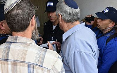 Police officers speak to protesters and residents of nine buildings found to have been built illegally in the Ofra settlement, which were due to be evicted on February 28, 2017. (Israel Police)