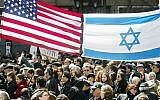 Demonstrators walking beneath Israeli and American flags at a pro-Israel rally at Dag Hammarskjold Plaza in New York City, April 7, 2002. (Mario Tama/Getty Images)