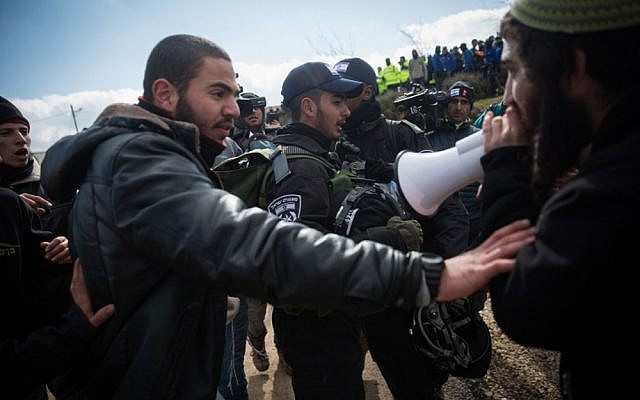 A resident of the Amona outpost shouts at police officers through a megaphone during the evacuation of the illegal settlement on February 1, 2017. (Hadas Parush/Flash90)