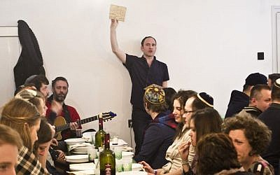 Adam Schonberger, standing, with other participants at the 2016 seder dinner at the Aurora Jewish community center in Budapest, April 22, 2016. (Courtesy of Marom via JTA)