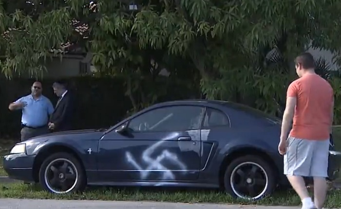 359164982beb Illustrative  A large swastika is spray-painted on the side of a car in