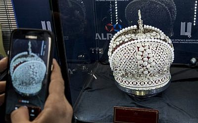 A diamond buyer takes a picture of a replica of Russian Queen Catherine the Great's imperial crown, on sale for $20 million during the International Diamond Week (IDW) in the Israeli city of Ramat Gan, east of Tel Aviv on February 14, 2017. / AFP PHOTO / JACK GUEZ