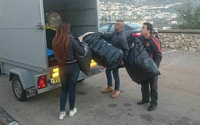 Israeli volunteers packing winter supplies to be delivered to Syrian refugees. (Operation Human Warmth)