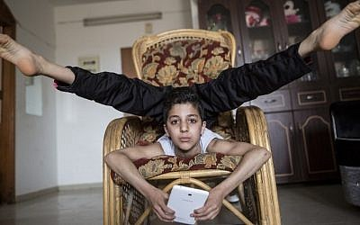 This file photo taken on April 28, 2016 shows then-twelve-year-old Palestinian teenager Mohammed al-Sheikh showing off his contortionist skills at his home in Gaza city. / AFP PHOTO / MAHMUD HAMS
