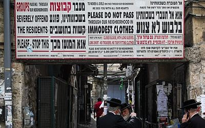 Ultra-Orthodox men stand under a sign stating that the entrance of groups and of people in clothes that are not modest offend the feeling of the citizens in Meah Shearim,  Jerusalem, on March 7, 2013. (Nati Shohat/Flash 90)
