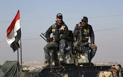 Two policemen sit atop of their armored vehicle as Iraqi Federal police deploy after regaining control of the town of Abu Saif, west of Mosul, Iraq, Wednesday, Feb. 22, 2017. (Khalid Mohammed/AP)
