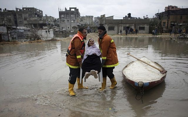 Palestinian rescue members evacuate a woman from her flooded home during a heavy rain storm in Jabaliya refugee camp, northern Gaza Strip, Thursday, Feb. 16, 2017. (AP/Khalil Hamra)