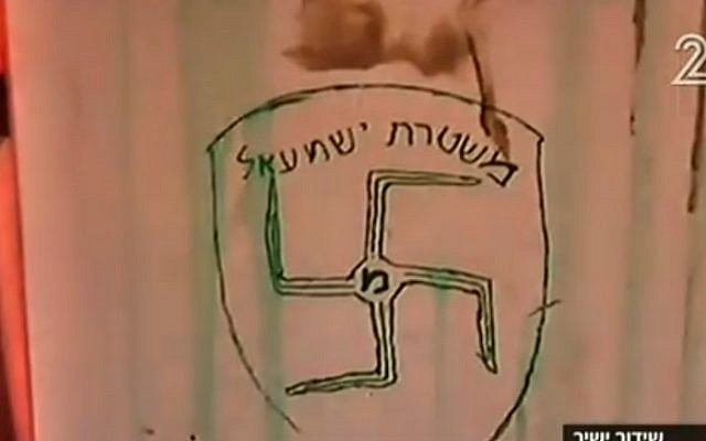 Graffiti daubed on the wall of Amona synagogue shows a swastika and the slogan 'Ishmael Police' -- a reference to the Israel Police force and to Ishmael, the son of the biblical patriarch Abraham believed by some to be the forebear of today's Arabs. (screen capture: Channel 2)