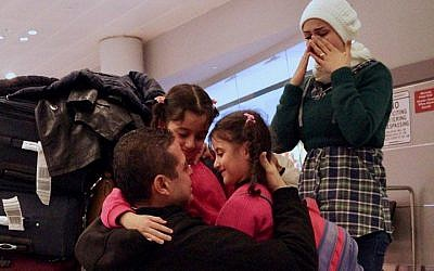 Fadi Kassar hugs his young daughters for the first time in over 2 years after his family was reunited at John F. Kennedy Airport in New York City, February 2, 2017. (Bill Swersey/HIAS)