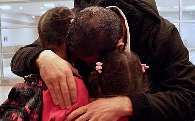 Fadi Kassar hugs his young daughters for the first time in over 2 years after his family was reunited at John F. Kennedy Airport in New York City on February 2, 2017. (Bill Swersey/HIAS)