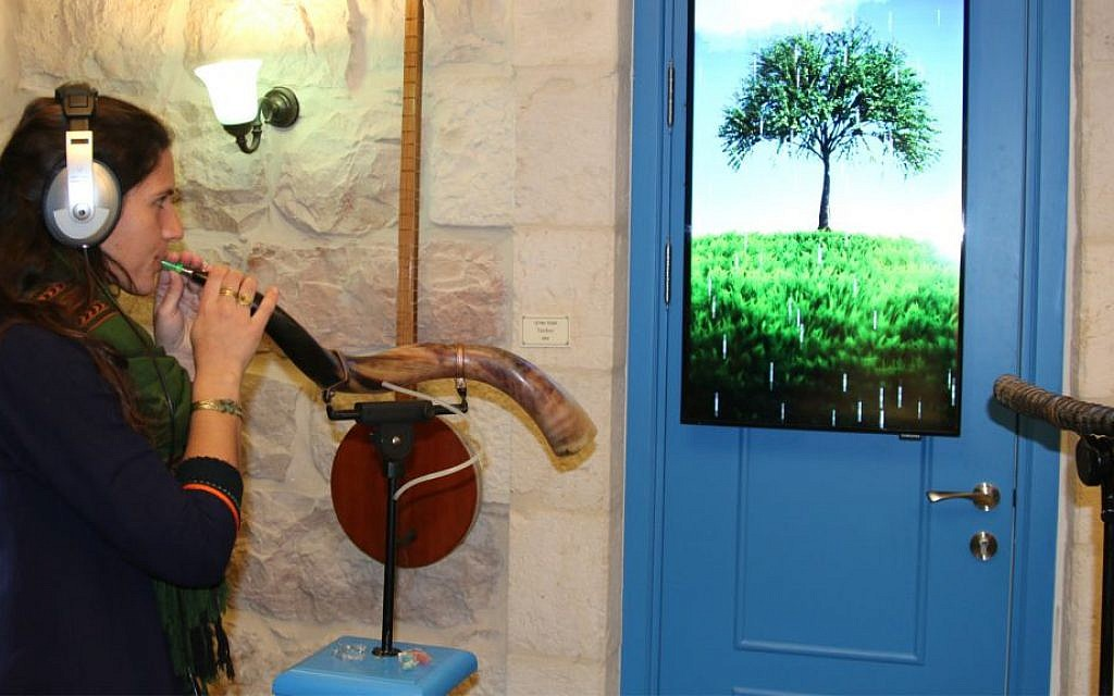 A tour guide plays a shofar in the Hebrew Music Museum. (Shmuel Bar-Am)