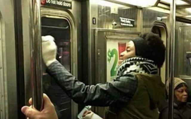 New York commuters scrub anti-Semitic graffiti from a subway car (YouTube screenshot)