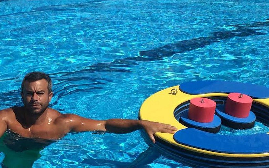 Asaf Ventura posing with his floating gym at an Israeli army rehabilitation center in Haifa, June 2015. (Courtesy Asaf Ventura via JTA)