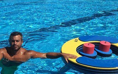 Asaf Ventura posing with his floating gym at an Israeli army rehabilitation center in Haifa, June 2015. (Courtesy Asaf Ventura via JTA)