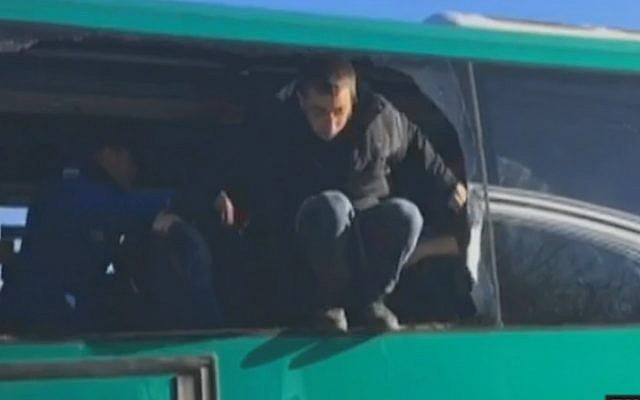 Protesters removed from the synagogue at Amona smash a window to escape after they were placed on a bus by police, during the outpost's evacuation on February 2, 2017 (screen capture: Channel 10)