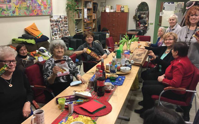 Seniors in Krakow, Poland enjoy Purim gift bags provided by Jewish Connection project delivered by Israeli travelers, March 2017. (Courtesy)