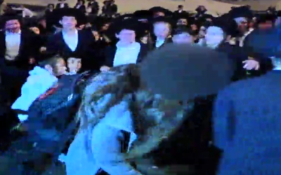 Ultra-Orthodox protesters attack a woman during anti-draft demonstrations in Jerusalem on March 28, 2017. (Screen capture: Reshet TV)