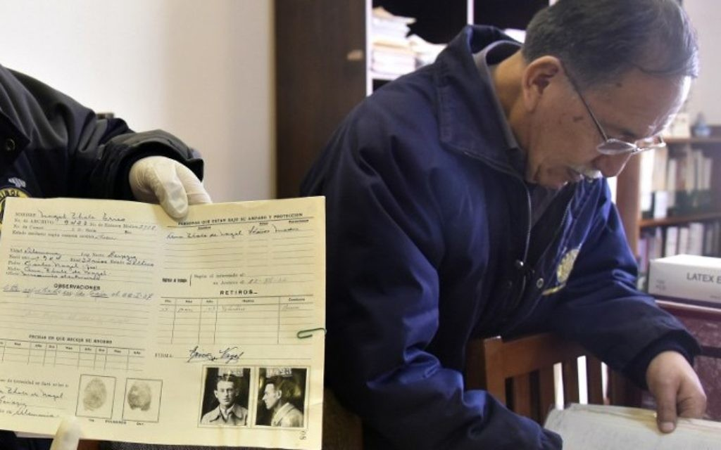 Edgar Ramirez right), the head of the archives in the Bolivian state mining company COMIBOL, with unearthed documents which reveal that Jewish-German tin baron Mauricio Hochschild helped thousands of Jews escape Nazism, in El Alto, Bolivia. (Aizar Raldes/AFP)