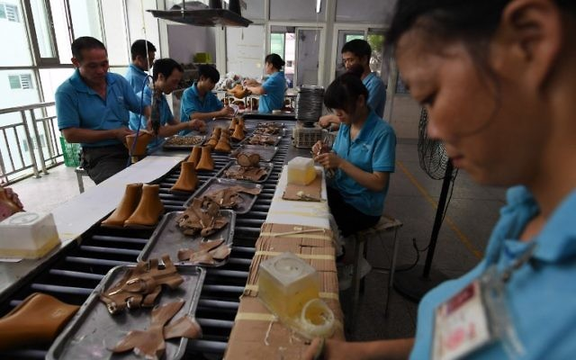 This photo taken on September 14, 2016 shows workers on a production line at the Huajian shoe factory, where about 100,000 pairs of Ivanka Trump-branded shoes have been made over the years amongst other brands, in Dongguan in south China's Guangdong province. (AFP PHOTO / Greg Baker)
