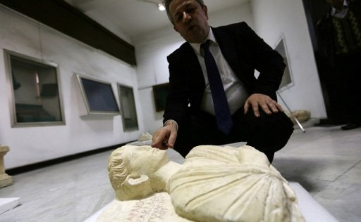 The director of Syria's Antiquities Department Maamun Abdul-Karim shows one of two rare busts rescued from the Islamic State group in the ancient city of Palmyra and restored in Italy, after they were returned to Syria, at the National Museum in Damascus on March 1, 2017. (Louai Beshara / AFP)