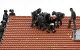 Israeli police remove protesters from the roof of a home slated to be destroyed in the West Bank settlement of Ofra on March 1, 2017. (AFP Photo/Menahem Kahana)