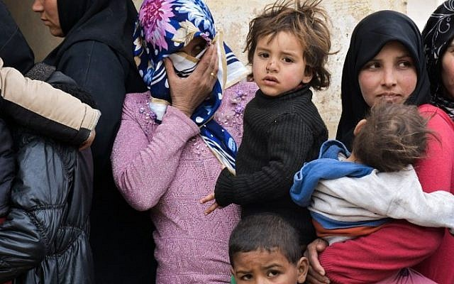 Displaced Syrian women queue up to receive medical aid and vaccines from Russian Army forces through pediatric field hospitals in the district of Jibreen, on the outskirts of the northern Syrian city of Aleppo on March 1, 2017. (AFP PHOTO / George OURFALIAN)