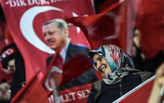 A woman stands near a flag bearing a Turkish President Recep Tayyip Erdogan's picture on March 5, 2017 in Istanbul during a pro-government women's meeting. (AFP Photo/Ozan Kose)