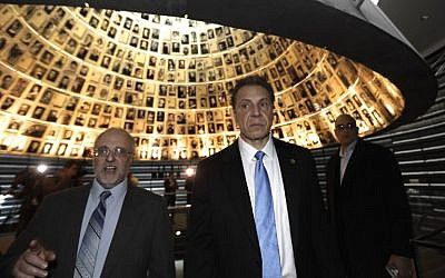 New York Governor Andrew Cuomo, center, looks at pictures of Jewish Holocaust victims on March 5, 2017, at the Hall of Names during his visit to the Yad Vashem Holocaust Memorial museum in Jerusalem.(AFP/MENAHEM KAHANA)