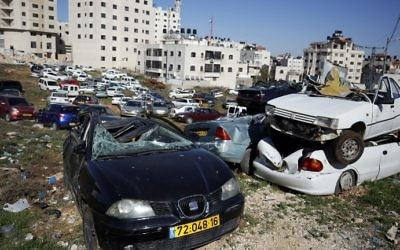 Wrecked cars with Israeli license plates are seen in the West Bank village of  al-Ram on March 6, 2017. (AFP Photo/Abbas Momani)
