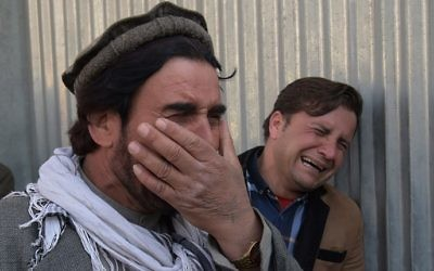Two Afghan men weep for their relatives in front of the main gate of a military hospital in Kabul on March 8, 2017, after a deadly six-hour attack claimed by the Islamic State group. (AFP PHOTO / SHAH MARAI)