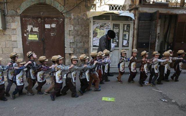 Ultra-Orthodox Jewish children wearing costumes march in line in the street during their school Purim celebration four days ahead of the official holiday on the Jewish calendar in the ultra-Orthodox Jewish neighborhood of Mea Shearim in Jerusalem on March 8, 2017.(AFP PHOTO / MENAHEM KAHANA)