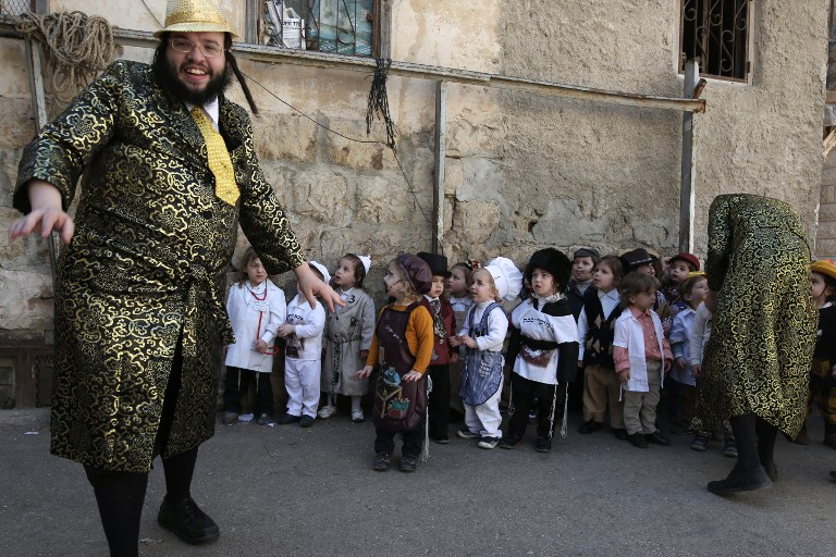 Ultra-Orthodox Jewish children wearing costumes stand in the street during their school Purim celebration four days ahead of the official holiday on the Jewish calendar in the ultra-Orthodox Jewish neighbourhood of Mea Shearim in Jerusalem on March 8, 2017.( AFP PHOTO / MENAHEM KAHANA)