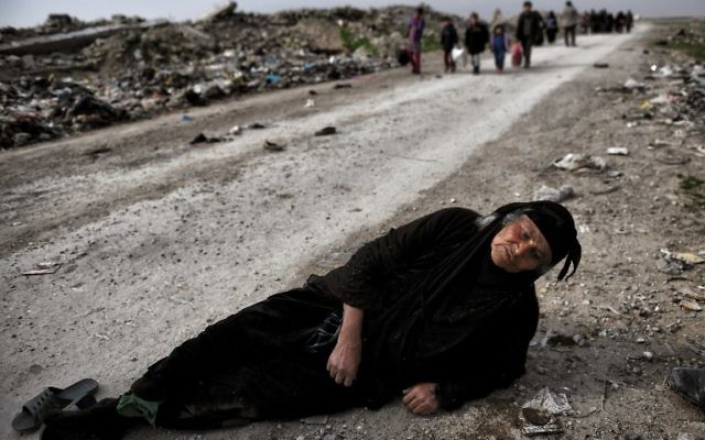 An Iraqi woman lies on the ground as civilians flee Mosul while Iraqi forces advance inside the city during fighting against Islamic State group's fighters on March 8, 2017. AFP PHOTO / ARIS MESSINIS