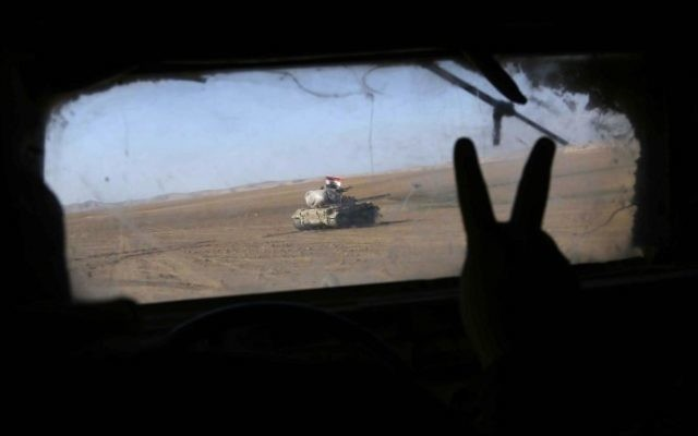 Iraqi government forces supported by fighters from the Abbas Brigade, which fight under the umbrella of the Shiite popular mobilization units, advance in village of Badush, some 15 kilometers northwest of Mosul, during the ongoing battle to retake the city's west from Islamic State (IS) jihadists on March 8, 2017. (AFP PHOTO / Mohammed SAWAF)