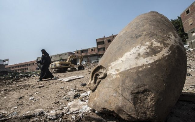 An Egyptian woman walks past the head of a statue at the site of a new discovery by a team of German-Egyptian archeologists in Cairo's Mattarya district on March 9, 2017. AFP/KHALED DESOUKI)