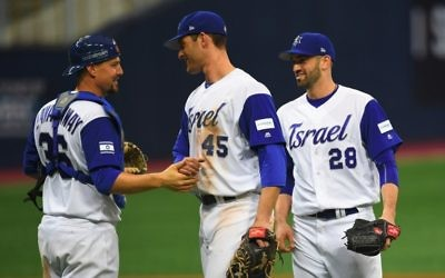 This file photo taken on March 9, 2017 shows Catcher Ryan Lavarnway (L) of Israel celebrating their victory with teammates pitcher Josh Zeid (R) and infielder Nate Freiman (C) against the Netherlands after their first round game of the World Baseball Classic at Gocheok Sky Dome in Seoul. (AFP PHOTO / JUNG Yeon-Je)