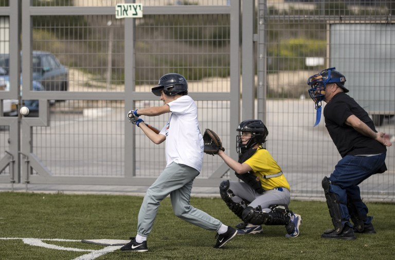 A young player from the Modiin team strikes the ball during a baseball match between Modiin and Jerusalem youth teams in the Israeli city of Modiin on March 10, 2017. (AFP PHOTO / JACK GUEZ)