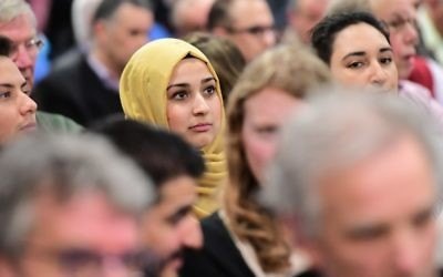 A woman looks on as people take part in a debate on role of Islam in the country ahead of the Dutch parliamentary elections at the Essalam mosque, the country's largest, in Rotterdam on March 10, 2017. (AFP PHOTO / EMMANUEL DUNAND)