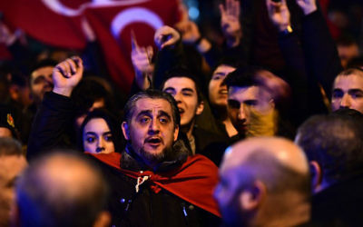 People gesture and wave flags as Turkish residents of the Netherlands gather for a protest outside Turkey's consulate in Rotterdam on March 11, 2017. (Emmanuel Dunand/AFP)