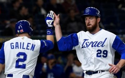 Israeli infielder Ike Davis (R) is congratulated by his teammate Blake Gailen (#2) after arriving at the home plate by a double of catcher Ryan Lavarnway during the World Baseball Classic Pool E second round match between Cuba and Israel at Tokyo Dome in Tokyo on March 12, 2017. (AFP PHOTO / TORU YAMANAKA)