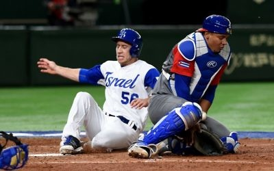 Israeli third baseman Ty Kelly (L) arrives at the home plate next to Cuban catcher Yosvani Alarcon after a single hit by right fielder Zach Borenstein at the top of the sixth inning during the World Baseball Classic Pool E second round match between Cuba and Israel at Tokyo Dome in Tokyo on March 12, 2017 (AFP PHOTO / TORU YAMANAKA)