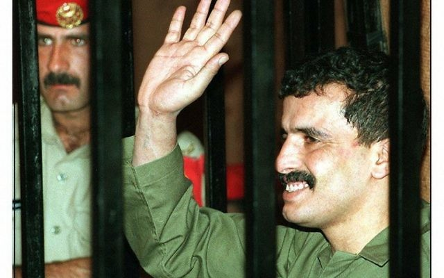 This file photo taken on June 25, 1997 shows Jordanian soldier Ahmad Musa Mustafa Dakamseh, waving to his family from behind  bars, during his hearing at a Amman military court.  Dakamseh was released on March 12, 2017 from the Bab al-Hawa prison in Irbid, 90 kilometres (60 miles) north of the capital Amman after serving 20 years in prison, a relative told AFP. In March 1997, he fired an automatic weapon at Israeli schoolgirls on a trip to the Jordan-Israel border, killing seven of them and wounding others and a teacher. He had been sentenced to life imprisonment. (AFP PHOTO / JAMAL NASRALLAH)