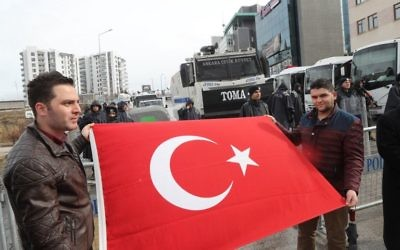 """Members of the Turkish association for International Peace and Friendship (Ubdder) and the ruling Justice and Development (AKP) party gather after putting a black wreath at a blockade of anti-riot police vehicles by the Dutch embassy (Rear R) after the area was sealed off for """"security reasons"""" as a crisis escalated between Turkey and The Netherlands after Turkey's Foreign minister was barred from speaking in the country to promote a referendum at home (AFP PHOTO / ADEM ALTAN)"""
